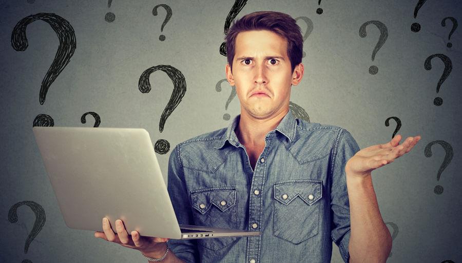 Schulterzuckender Mann mit Computer
